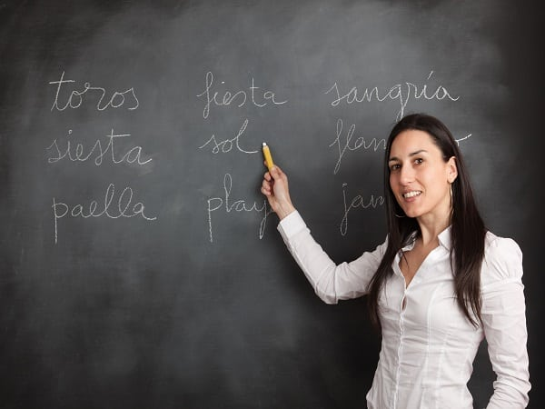 teacher writting on a black board words in spanish